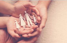 Handen houden een uit papier geknipt figuur wat een gezin voorstelt vast