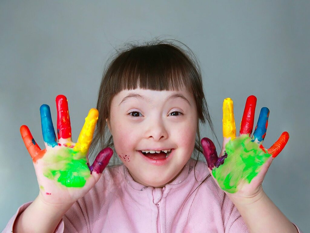 Verstandelijk beperkt meisje dat haar handen laat zien, die met kleurrijke verf bedekt zijn.