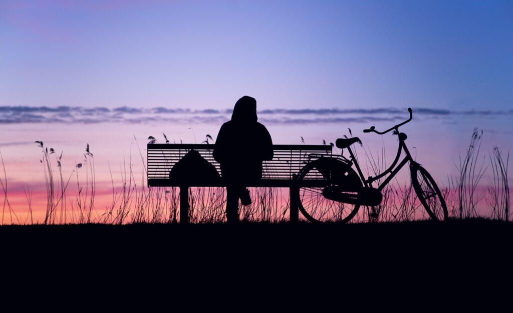 Iemand zit alleen op een bankje in het donker met fiets naast zich
