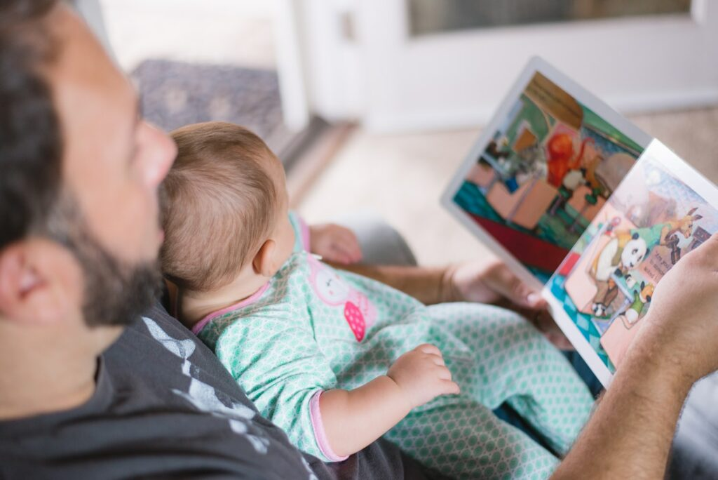 Vader leest prentenboek voor aan baby