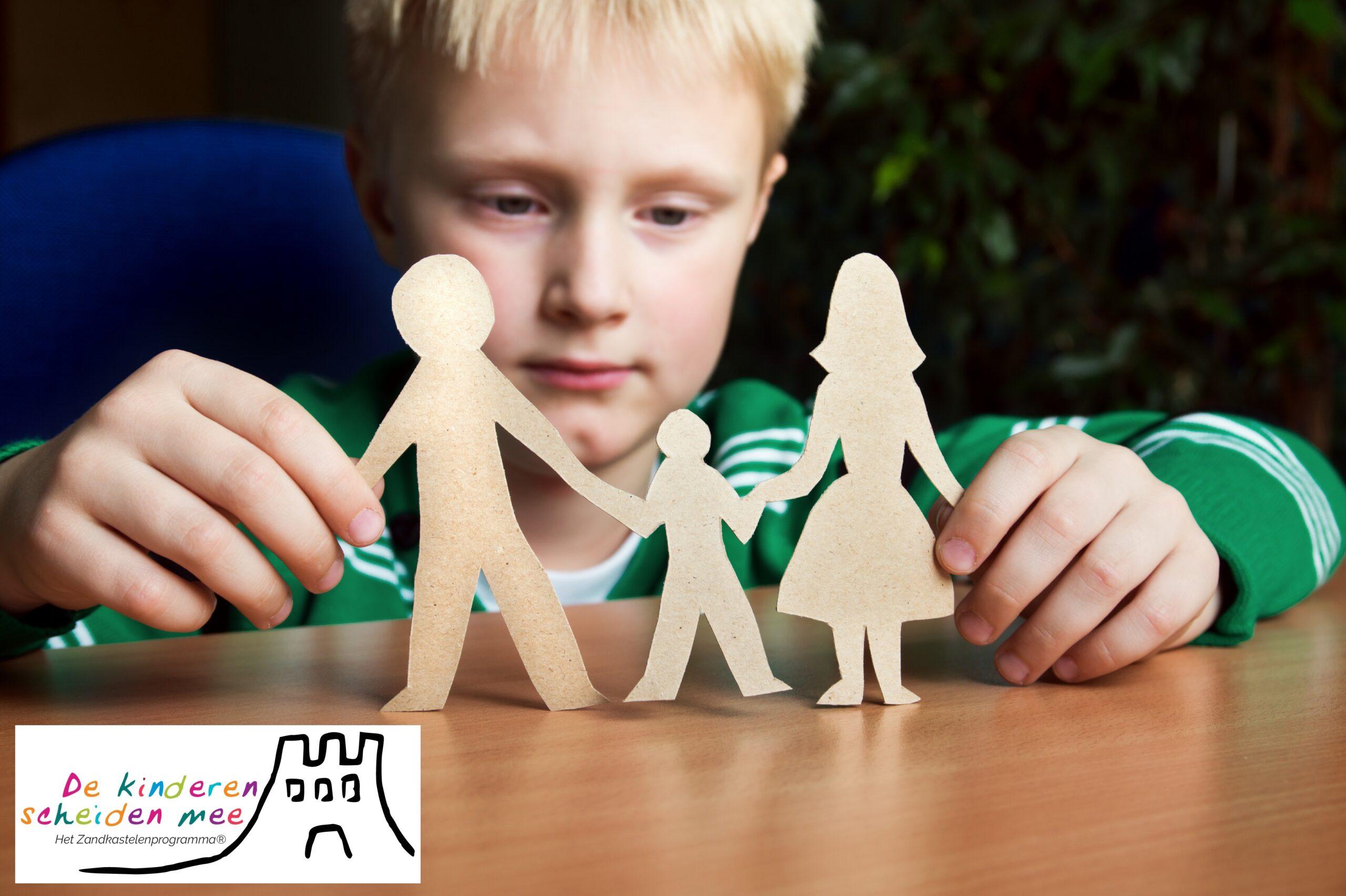 Jongetje speelt met geknipte papieren poppetjes die ouders met kind voorstellen
