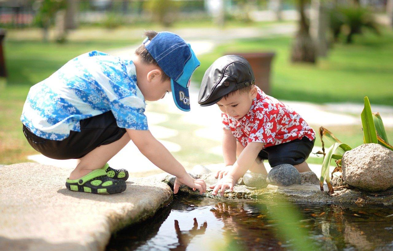 Twee jongetjes met petje op spelen bij vijver