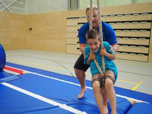 Jongen in gymzaal slingert in de touwen waarbij volwassene helpt