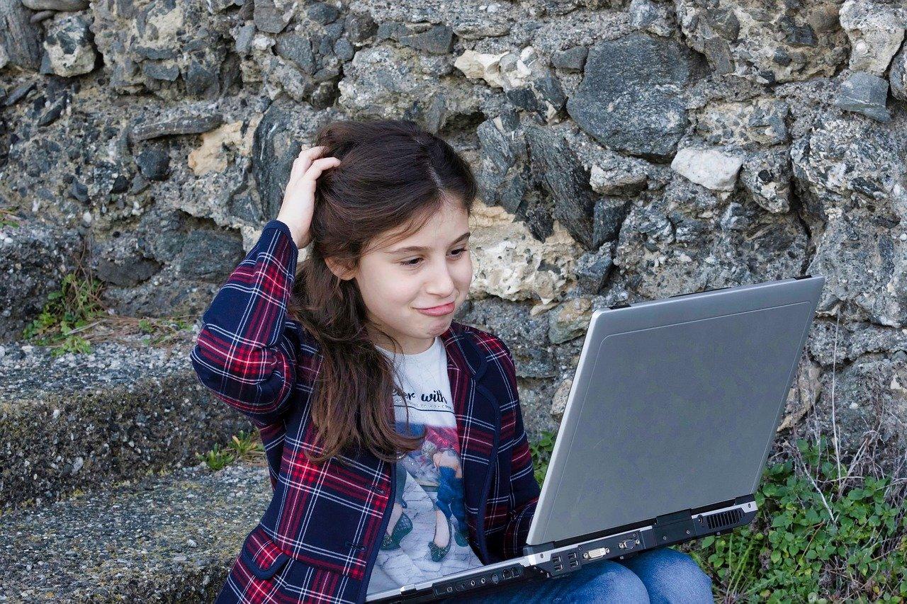 Meisje met laptop op schoot