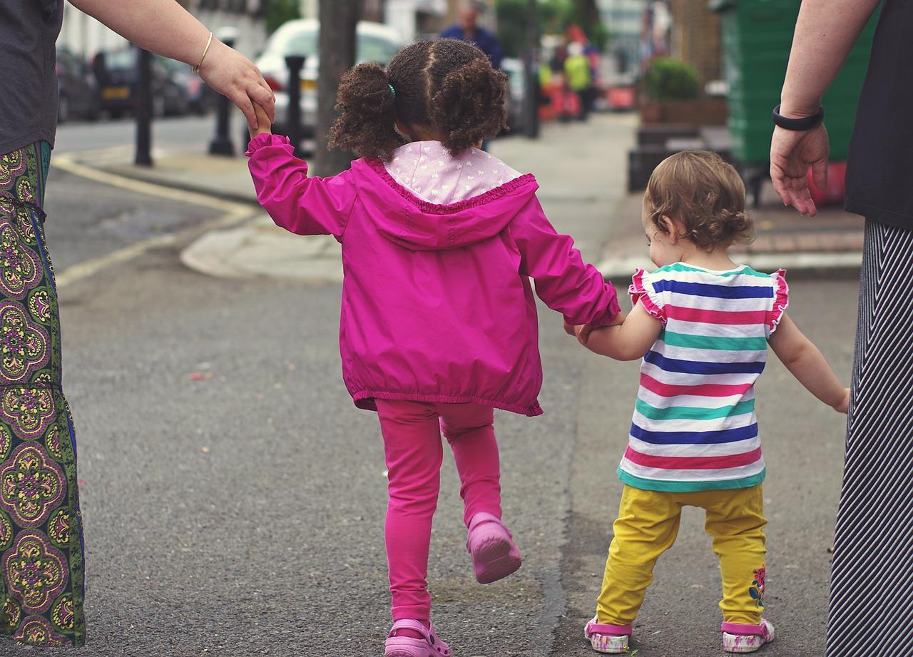 twee kindjes lopen hand in hand, van achteren gezien