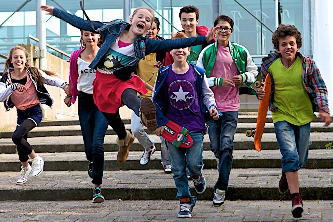 groepje van acht blije kinderen met skateboards komen aanrennen