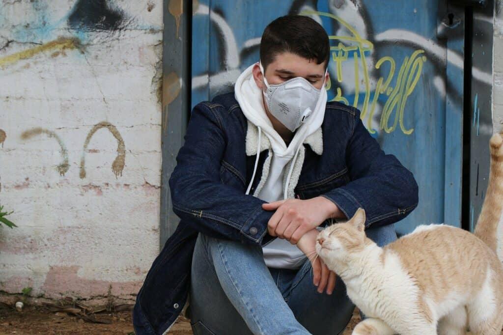 Op de grond zittende jongen met mondmasker aait kat