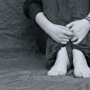 persoon met opgetrokken benen op de bank