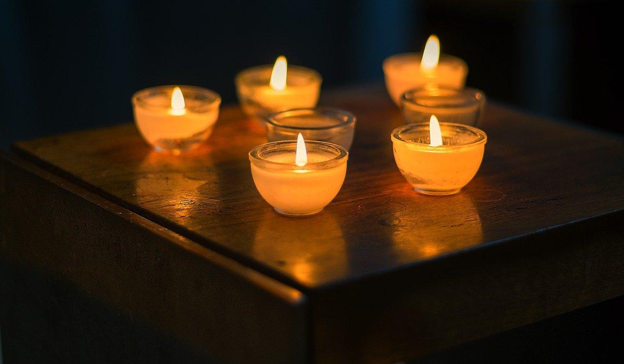 vijf brandende kaarsjes in een doorzichtig bakje op een tafel