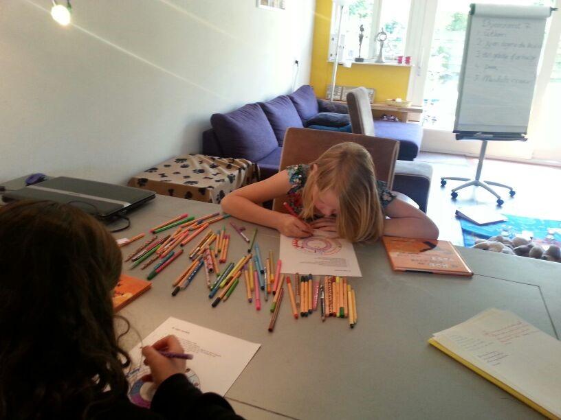 Twee kinderen kleuren tekening in aan grote tafel