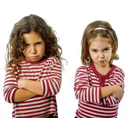 Twee booskijkende meisjes met armen over elkaar