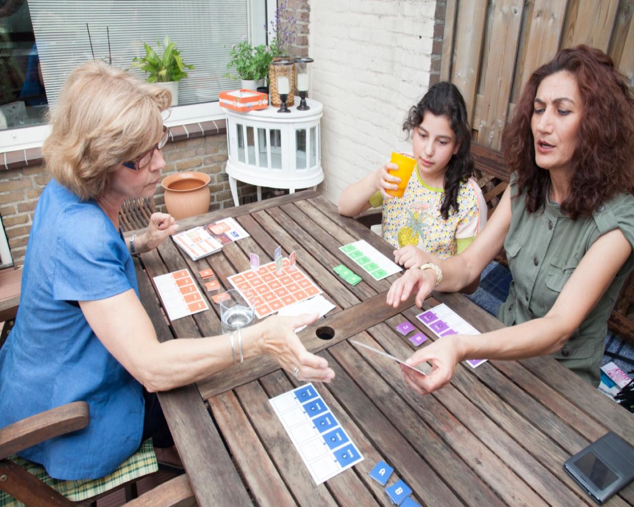 twee volwassen vrouwen en een kind doen een letterspel aan een tafel in de tuin