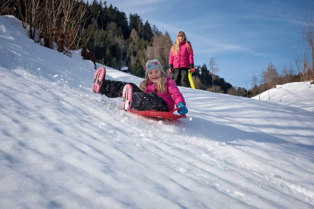 Meisje op slee in de sneeuw glijdt een heuvel af