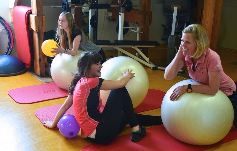 twee kinderen en leraar in gymruimte sporten met bal