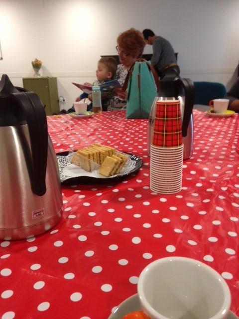 Koekjes en koffie staan klaar op tafel met rood/wit gestippeld tafelkleed met op de achtergrond een moeder met kindje