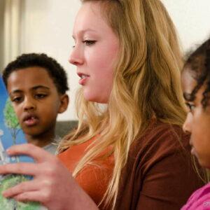 Jonge vrouw leest twee kinderen voor uit kinderboek