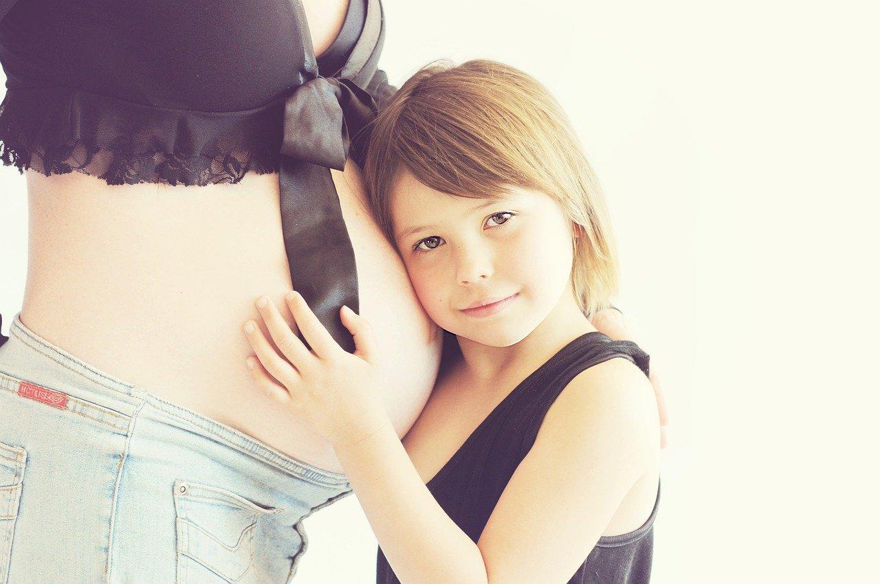 Meisje leunt met hoofd tegen de buik van zwangere moeder