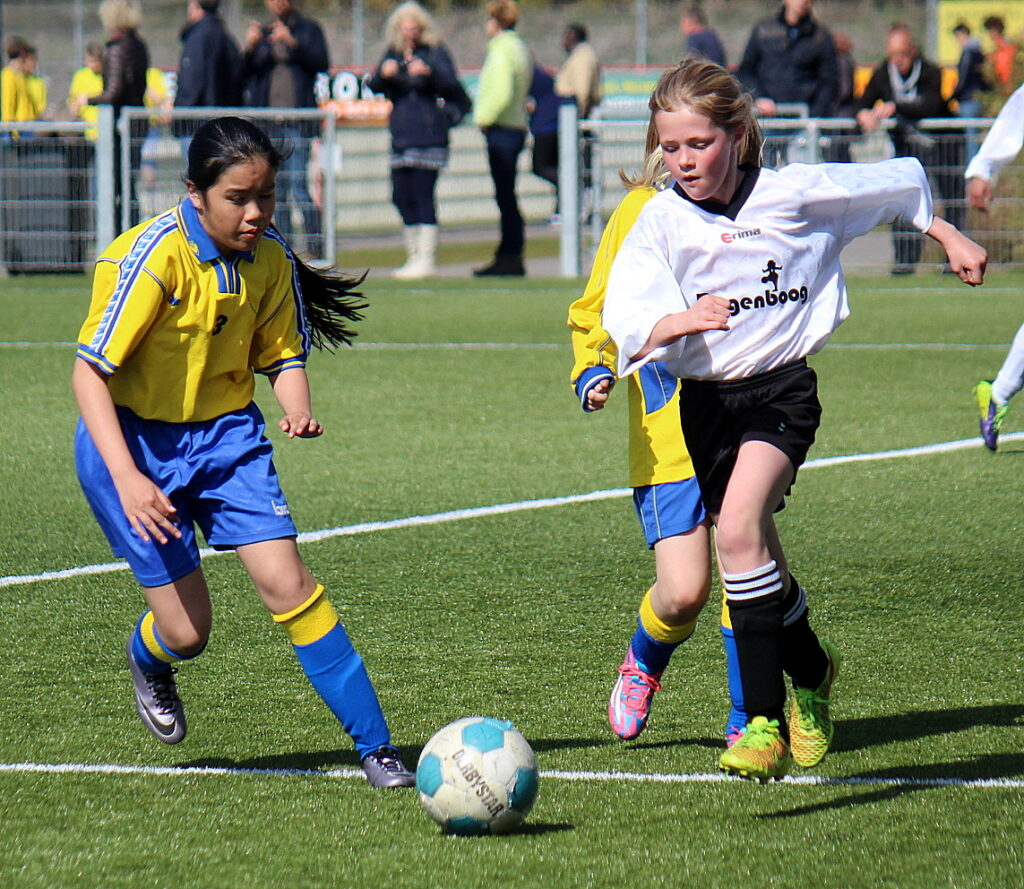 Voetballende meisjes op sportveld