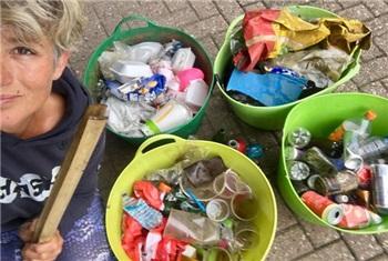 Kind met bakjes opgeruimd afval