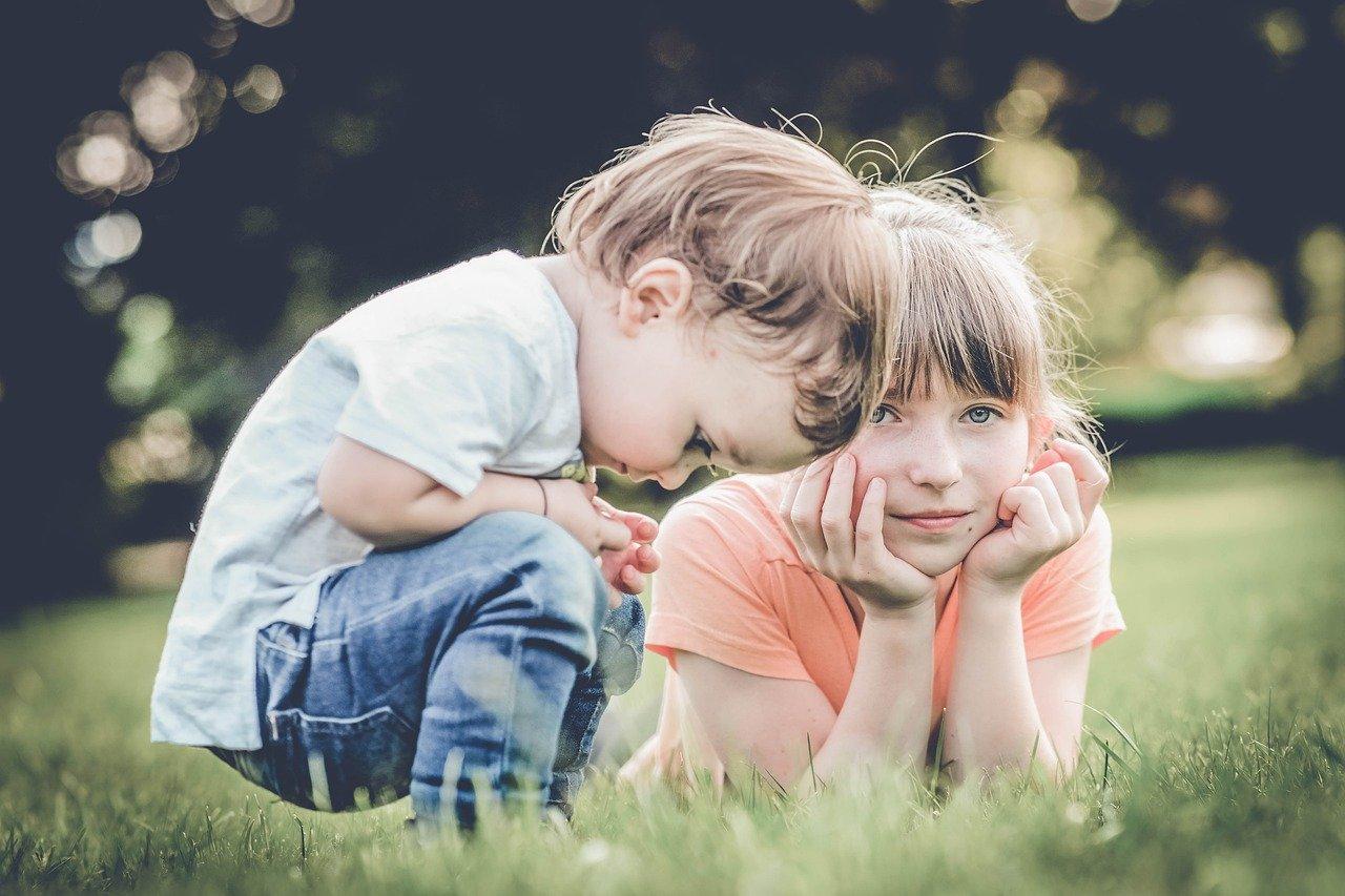 peuter en basisschool kind zitten in het gras