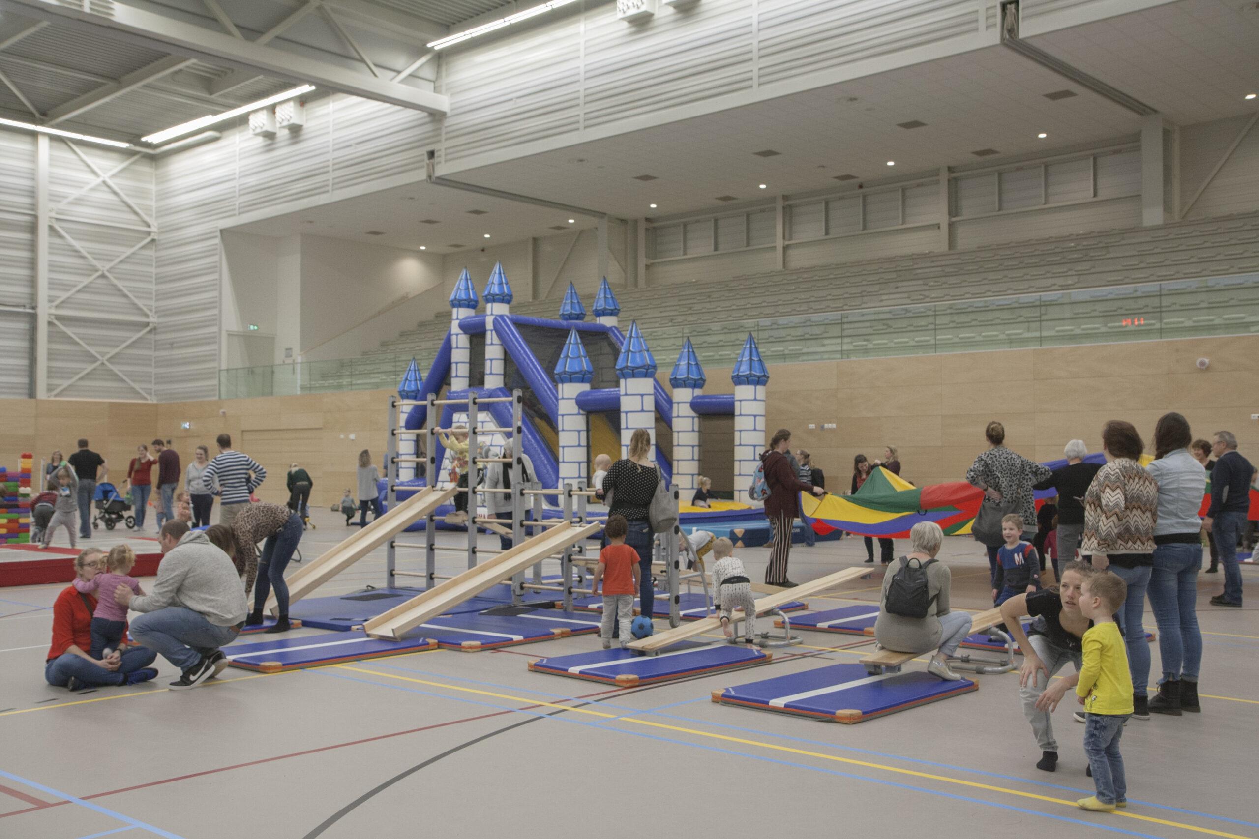 Spelende en sportende kinderen in sporthal