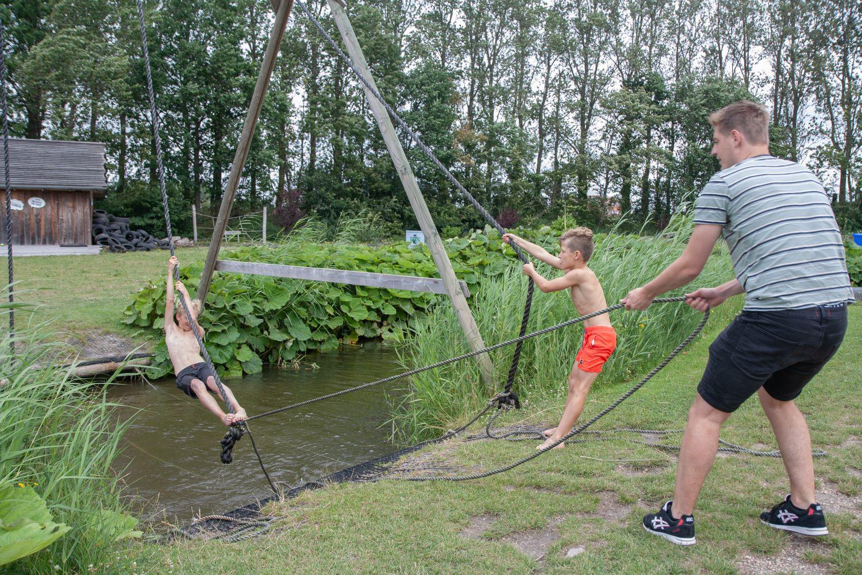 Een volwassene met twee kinderen met touwen over een sloot