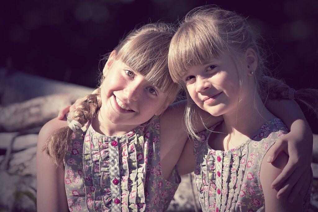 Twee zusjes armen om elkaar heen