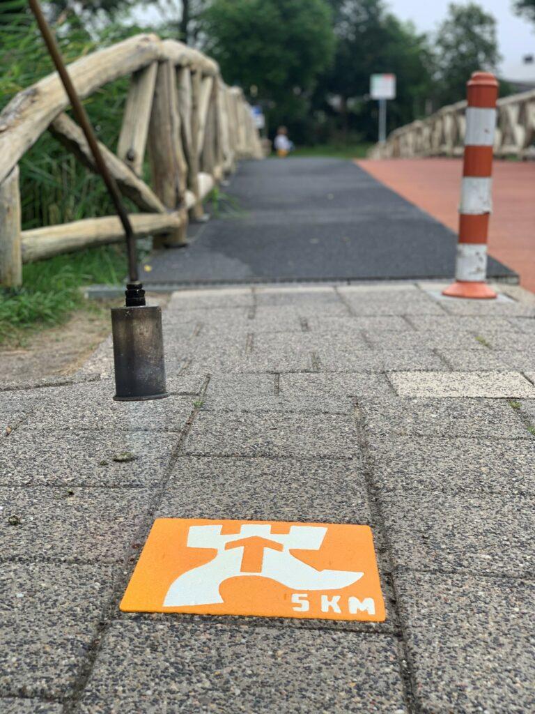 Stoep met 1 gekleurde stoeptegel die een wandelroute aangeeft