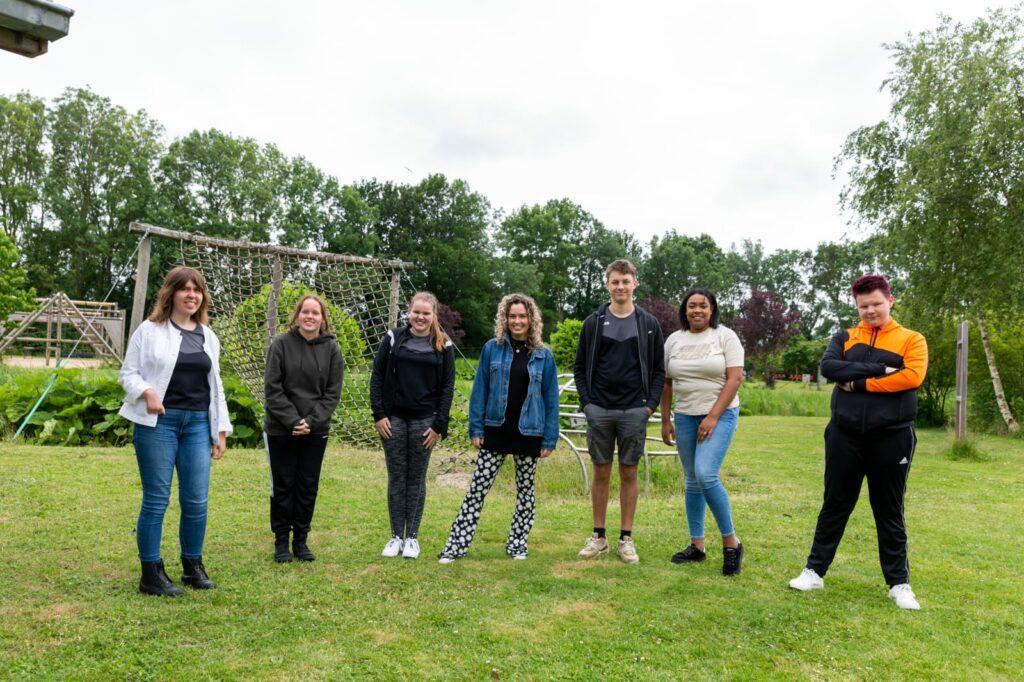 Zeven jongeren op een rij buiten op een sportveld