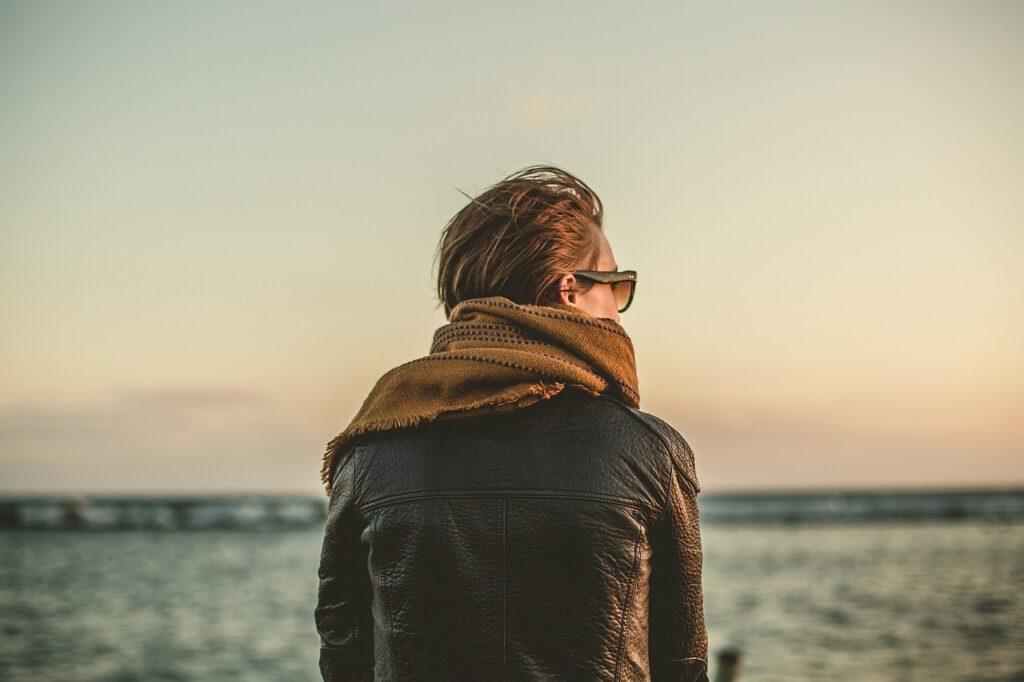 Vrouw zit aan het strand en kijkt uit over zee