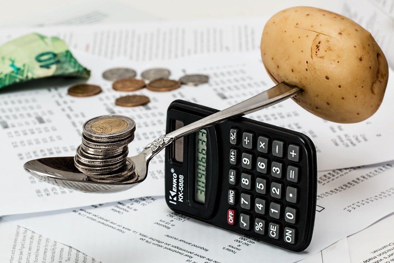 Telefoon, rekeningen, lepel die uit een aardappel steekt, en gevuld is met munten