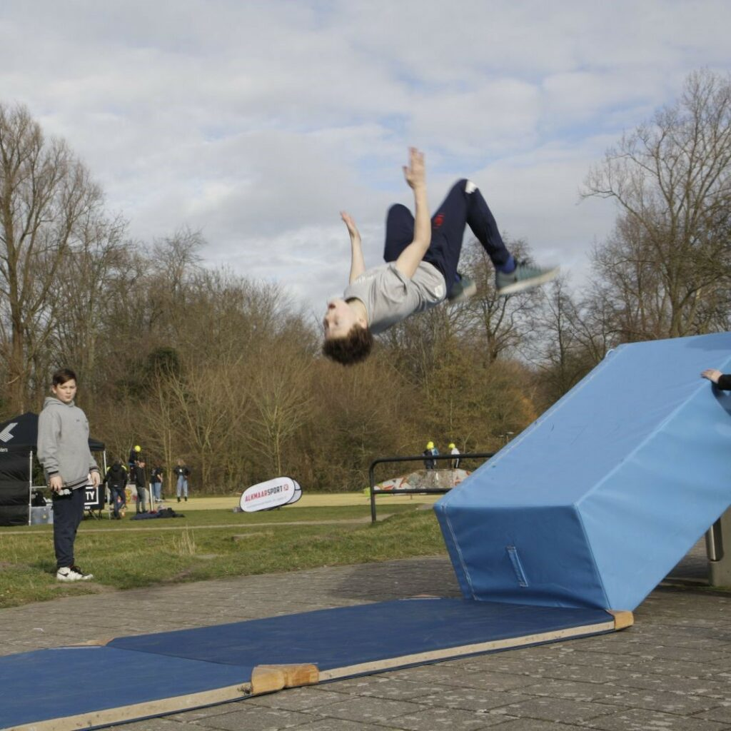 sportende kinderen op outdoor sportveld tijdens freerunning clinic