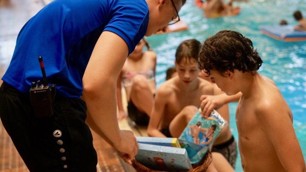 Kinderen in zwembad, badmeester laat plastic speelattributen (nog in verpakking) zien