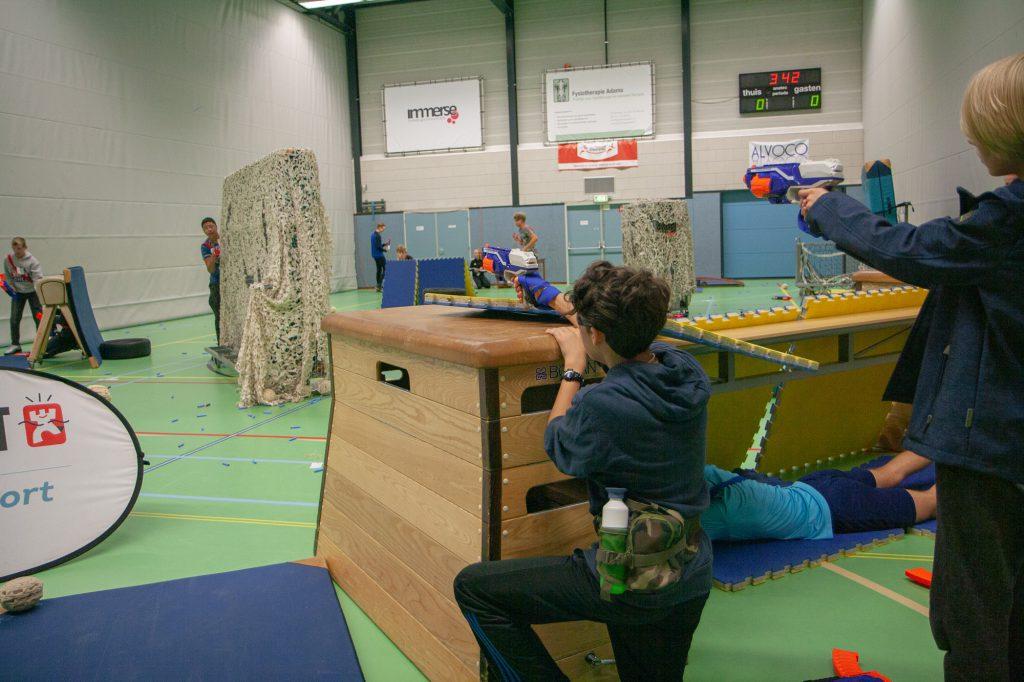Kinderen in gymzaal met sportattrubuten