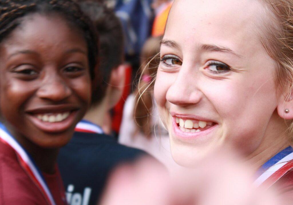 twee lachende meisjes die allebei een (sport)medaille om hun nek hebben