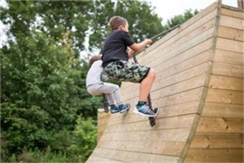 Twee jongetjes klimmen met touwen over houten obstakel